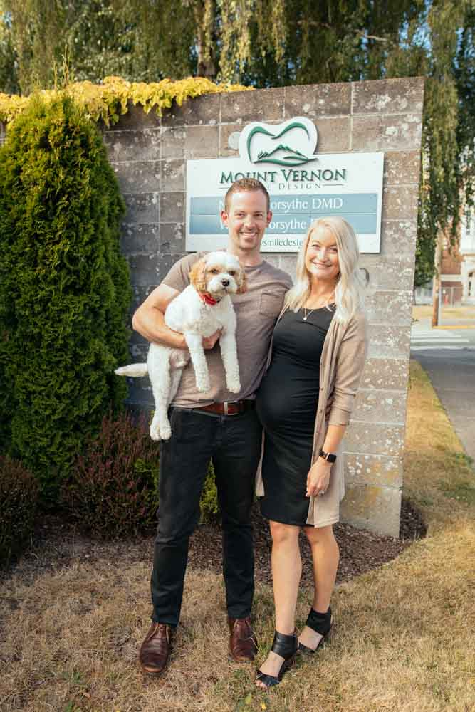 Drs. Nick and Whitney Forsythe stand near a sign for their dental practice with their dog