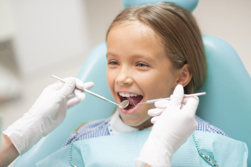 A young girl sits in a dental exam chair receiving a checkup