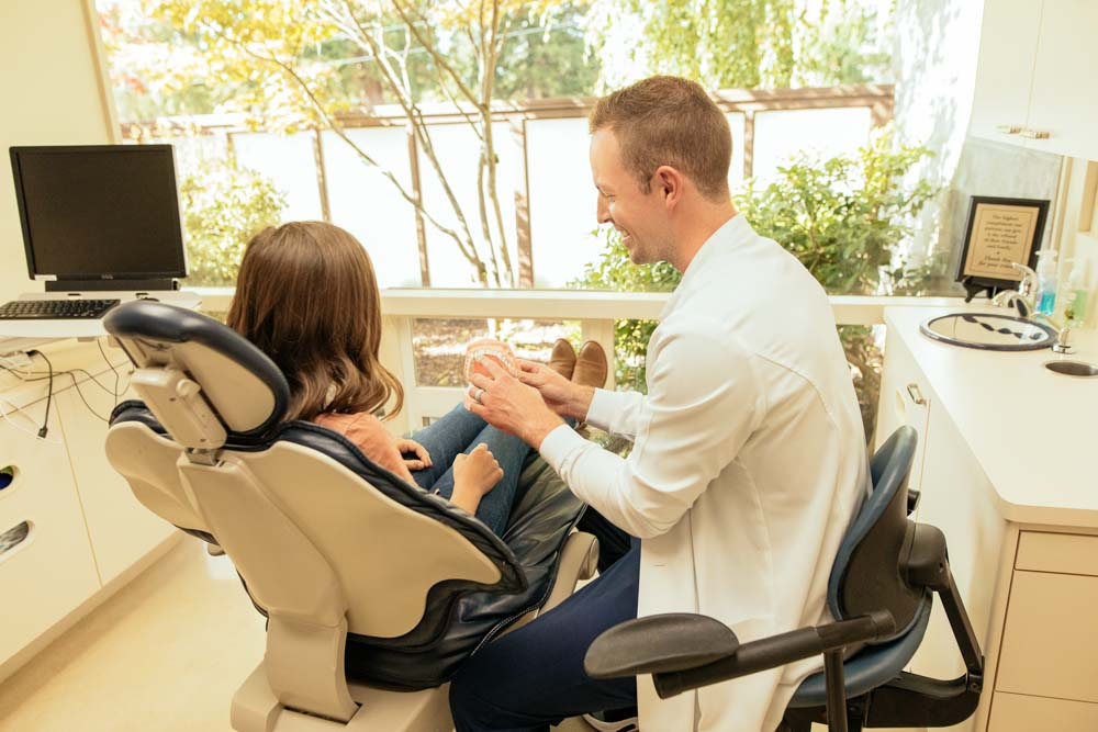 Dr. Nick Forsythe holds a model of teeth while speaking to a dental patient who is seated in an exam chair