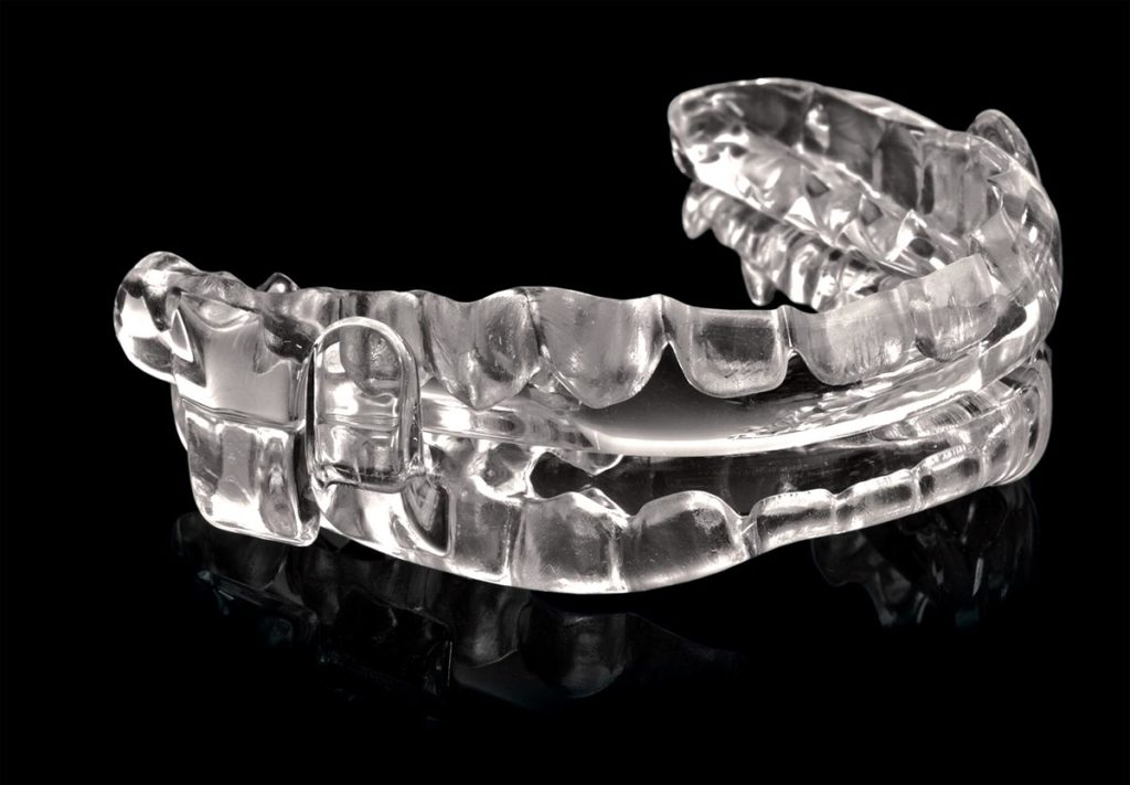 Clear oral appliance sits on a black background