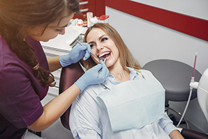 female dental patient sits in the dental chair for a teeth cleaning and dental checkup