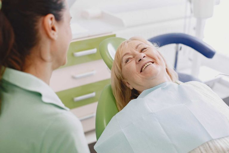 senior-aged female patient sitting at the dentist office